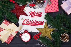 Frame of Christmas tree branches, gift boxes, red clocks and Christmas toys around a white sheet of paper