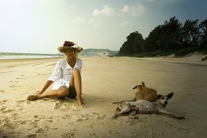 Girl in hat with dogs on the beach