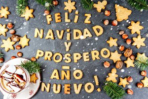 FELIZ NAVIDAD EN SPANISH COOKIES. Words Merry Christmas and happy new year en Spanish with baked cookies, Christmas card for hispanic countries top view. Snow effect