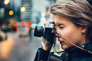 woman taking photo in city