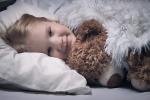 Little girl with toy bear. Sleepy baby is smiling under blanket
