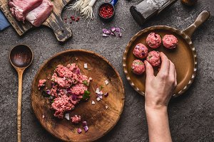 Hand puts meat ball in frying pan