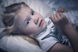 Little girl in bed at night not sleeping. Portrait