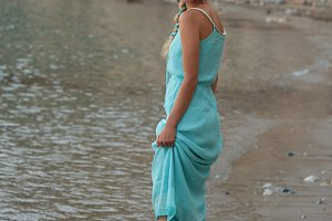 Young blonde woman with braided hear  wearing turquoise walking