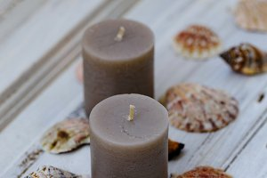 Two gray candles with seashells
