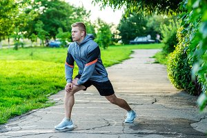 A male athlete warms up before jogging in the park. Listens to music on headphones.