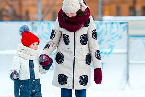 Little adorable girl with mother skating on ice-rink with mother