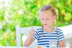 Adorable little girl having breakfast at cafe with sea view early in the morning