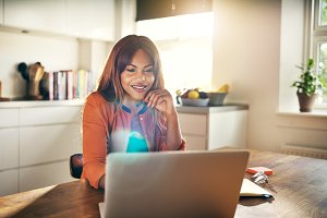 Smiling young female entrepreneur working online at her kitchen table
