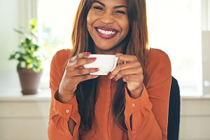 Smiling entrepreneur drinking coffee while working in her home office
