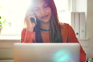 Smiling woman talking on a cellphone while working from home