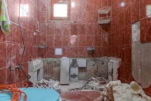 Damaged interior of old bathroom with red tiles