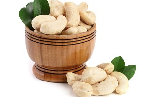Cashew in a wooden bowl with leaf isolated on white background