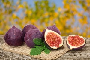 fig fruits with leaves on old wooden board with blurred garden background