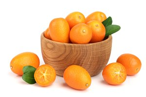Cumquat or kumquat with leaf in wooden bowl isolated on white background close up
