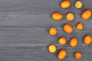 Cumquat or kumquat with half on black wooden background with copy space for your text. Top view. Flat lay pattern