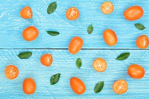 Cumquat or kumquat with leaf on blue wooden background. Top view. Flat lay pattern
