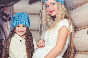 Happy loving family. Mother and her daughter child girl hugging. In expectation of childbirth, pregnancy. in a winter sweater and hat, the concept of Christmas.