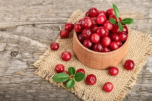 Cranberry with leaf in bowl on old wooden background