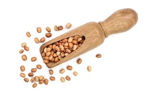 soybeans in a wooden scoop isolated on white background top view