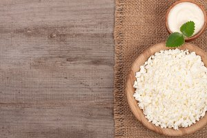 Cottage cheese in a wooden bowl with sour cream on old wooden background with copy space for your text. Top view