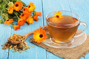 Calendula tea with fresh and dried flowers on blue wooden background