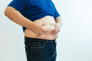 Fat man pinching his excessive fat on belly over white isolated background