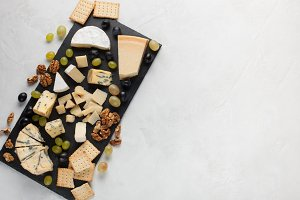 Assorted cheeses with white grapes, walnuts, crackers and on a stone Board. Food for a romantic date on a light background. Top view
