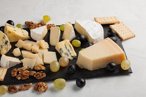 Assorted cheeses with white grapes, walnuts, crackers and on a stone Board. Food for a romantic date on a light background