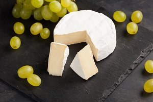 Cutting board of camembert cheese and white grapes on dark stone background