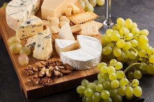 Assorted cheeses with white grapes, walnuts, crackers and white wine on a wooden Board. Food for a romantic date on a dark stone background. Top view
