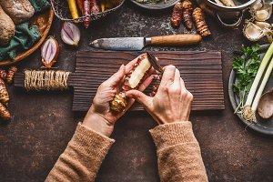 Hands peeling Jerusalem artichokes