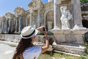Woman traveller shooting ancient statue with mobile phone