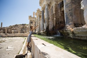Woman traveller making splashes of water at ancient fountain of