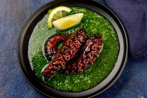 Grilled octopus serves with grin sauce on black plate. Stone blue background. Seafood. Top view