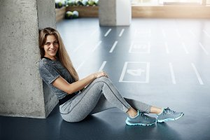 Young fit woman sitting in gym before a team workout. Fitness trainer having a rest. Sports concept.