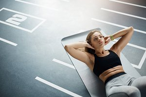 Beautiful adult fit woman doing abs crunches to get her body ready for summer. Healthy sport concept.