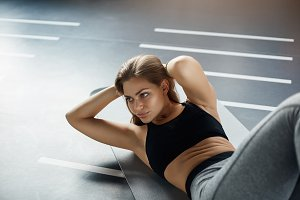 Posh young woman doing abs crunches to prepare her body for the summer. Fitness concept.