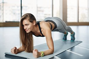 Beautiful woman doing push ups in fitness gym smiling. Getting her body in perfect shape.