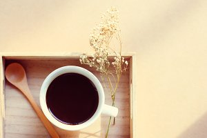 Black coffee on wooden tray