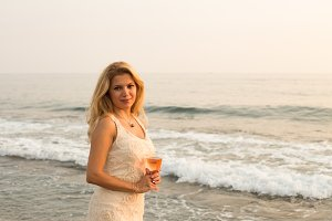 Beautiful blonde lady with a glass of pink wine by seaside