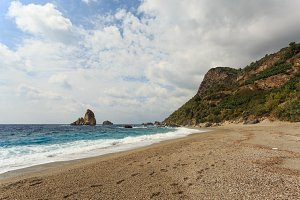 Paradise beach with mountain by the sea and rock islands in the