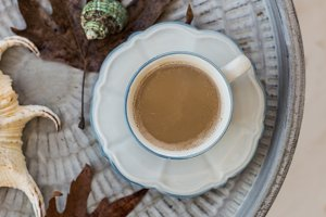 Cup of coffee with milk and autumn leaves