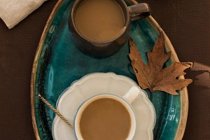 2 cups of coffee on turquoise ceramic tray with autumn leave