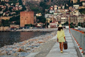 Summer travel concept. Traveller woman with brown vintage suitca
