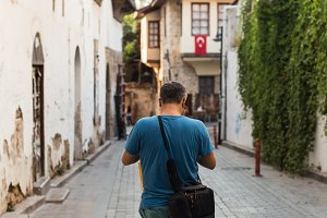 Traveller with camera bag walking through the narrow streets of