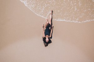 Aerial of Girl tanning on beach