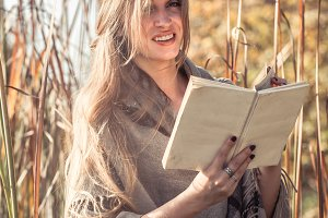 beautiful girl reading a book in autumn forest