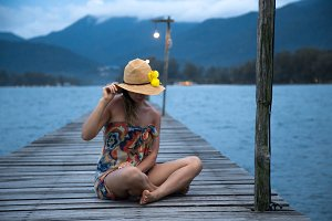 girl in a hat sitting on a long wooden pier in the evening