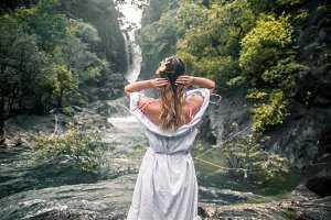 the girl looks at the waterfall back
